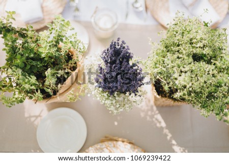 on festive table in wedding banquet area are plates, glasses, candles, cutlery, the table is decorated with compositions from greens and napkins