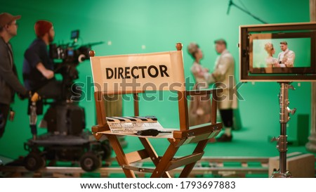 On Film Studio Set Focus on Empty Director's Chair. In the Background Professional Crew Shooting Historic Movie, Cameraman on Railway Trolley Shooting Green Screen Scene with Actors for History Movie Сток-фото ©