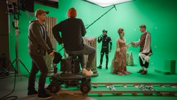 On Film Studio Set Shooting History Movie Green Screen Scene. Moving Cameraman on Railway Trolley Shooting Two Costumed Actors while Director Controls Process. Crew on Big Budget Filmmaking
