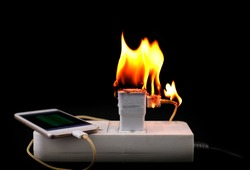 On fire Adapter smart phone charger at plug in power outlet at black background