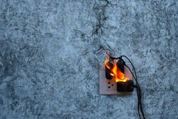 On fire charger adapter on the concrete wall exposed concrete background with copy space