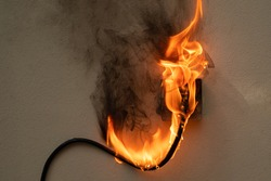 On fire electric wire plug Receptacle on the concrete wall background