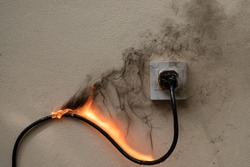 On fire electric wire plug Receptacle on the concrete wall exposed concrete background with copy space