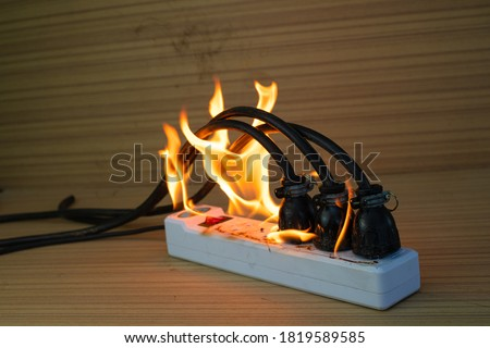 On fire multi socket with the connected power strip with a bunch of plugs on wood background Foto stock ©