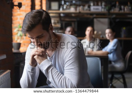 On foreground sad caucasian millennial guy outcast sitting separately from other diverse friends in cafe feels unhappy having communications difficulties, diffidence, jealousy, discrimination concept