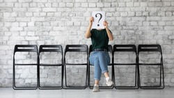 On grey brick wall background anonymous young woman sit on chair hiding her face behind paper with interrogation symbol. Doubtful female holding question mark sheet, problems and solutions HR concept