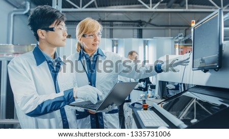 On High Tech Factory Worker Load Reels into Pick and Place Machine, Engineers Use Computer for Programming Electronic Machinery for Printed Circuit Board Assembly Line. Production of PCB SMT Machinery