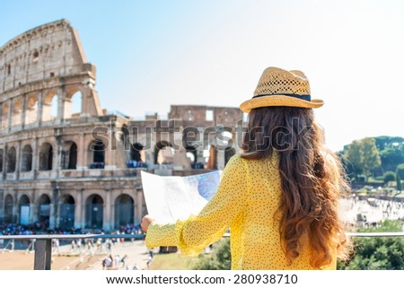 On hot summer's day, a woman is seen from behind and is holding a map of Rome. She is looking out onto Rome's Colosseum and the tourist crowds below.
