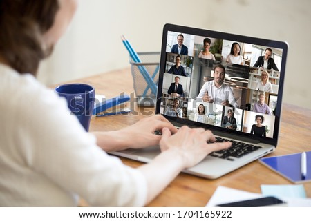 On laptop screen web cam view diverse age and ethnicity businesspeople taking part at group videocall, view over woman shoulder sit at desk working from home. Distant communication, modern app concept