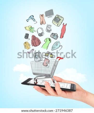 On line shop concept. Female hand holding a phone on which stands empty shopping cart with colorful drawing goods. E-commerce.