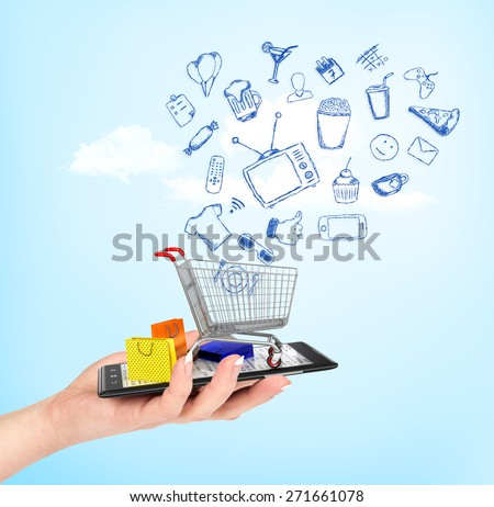 On line shop concept. Female hand holding a phone on which stands empty shopping cart with falling drawing icons and colorful package. E-commerce.