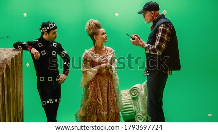 On Period Costume Drama Film Set: Beautiful Smiling Actress Wearing Renaissance Dress and Actor Wearing Motion Capture Suit Listen to Movie Director Explaining to Her Scene Context.