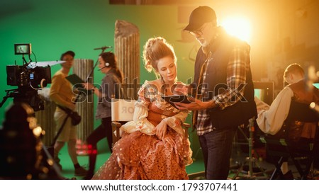 On Period Costume Drama Film Set: Beautiful Smiling Actress Wearing Renaissance Dress Sitting on a Chair Listens to Movie Director Explaining to Her Scene Context. High Budget Period Drama.