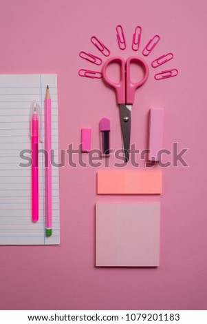 On pink background, school accessories and a pen, colored pencils, a pair of compasses, a pair of compasses, a pair of scissors. Copy space, top view #1079201183