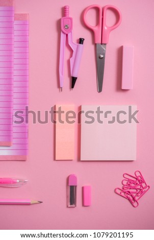 On pink background, school accessories and a pen, colored pencils, a pair of compasses, a pair of compasses, a pair of scissors. Copy space, top view #1079201195