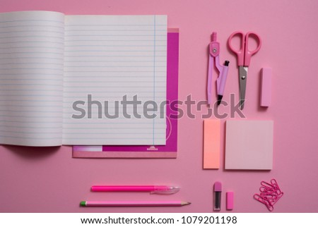 On pink background, school accessories and a pen, colored pencils, a pair of compasses, a pair of compasses, a pair of scissors. Copy space, top view #1079201198