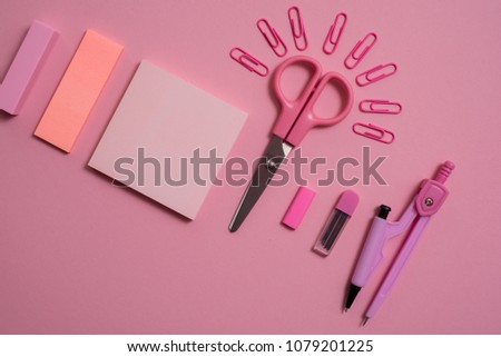 On pink background, school accessories and a pen, colored pencils, a pair of compasses, a pair of compasses, a pair of scissors. Copy space, top view #1079201225