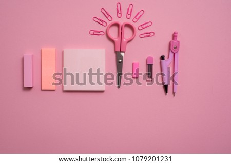 On pink background, school accessories and a pen, colored pencils, a pair of compasses, a pair of compasses, a pair of scissors. Copy space, top view #1079201231
