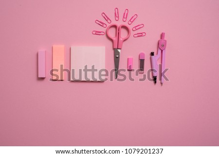 On pink background, school accessories and a pen, colored pencils, a pair of compasses, a pair of compasses, a pair of scissors. Copy space, top view #1079201237