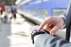 On platform station a man using his smartwatch. Close-up hands