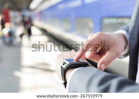 On platform station a man using his smartwatch. Close-up hands