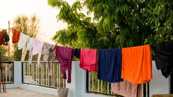 On roof, Rope with clean clothes outdoors on laundry day. Colorful clothes hanging in clothesline.