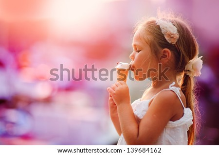 On seacoast the girl eats ice-cream at yachts background