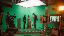 On Set: Director Explains Scene to Woman Actress Playing Renaissance Lady and Actor Wearing Motion Capture Suit. On Big Film Studio Professional Crew Shooting Period Costume Drama Movie.