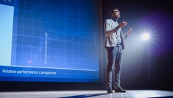 On-Stage: Speaker Does Presentation of the New Electronic Product, Shows Infographics, Statistic Animation on Screen. Auditorium Hall Live Event, Start-up Conference, Device Presentation and Release