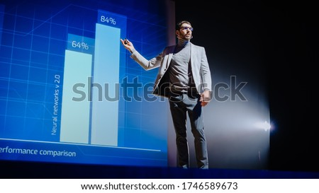 On-Stage Speaker Gives Presentation of Technological Device, Shows Infographics Animation on Big Screen. Auditorium Hall Live Event, Product Release, Start-up Conference. Low Angle