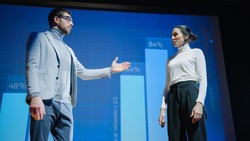 On Stage, Successful Female Executive and Male Manager Present New Product, Show Infographics, Statistics on Big Screen, Talk About Growth. Live Event, Tech Startup, Business Conference