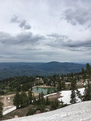 On summit of a mountain looking down onto a valley and emerald coloured lake, pine trees and stormy clouds. View of Wasatch Mountains, Little Cottonwood Canyon, Utah.