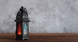 On table top image of decorations Ramadan Kareem holiday background.Close up Arabic lantern metal on brown wooden.Lighing sign for Muslim or Isiam religion.copy space for creative design.