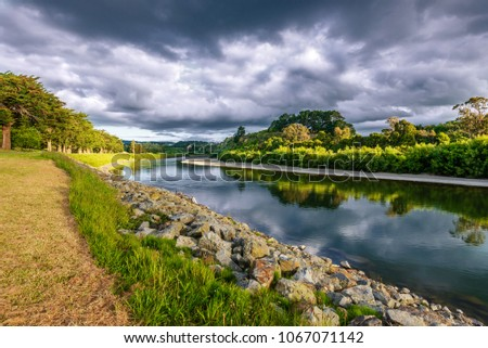 On the banks of the river Manawatu in Palmerston North New Zealand under dramatic skies