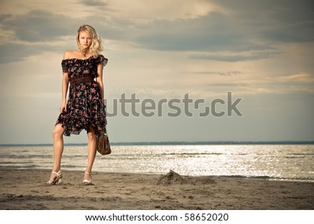 On the beach. A young pretty lady standing against the background of a seashore.