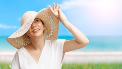 On the beach Portrait of beautiful young asian woman wearing straw hat wide brim to protect her lovely face from ultraviolet in the sunlight. Facial Sunscreens, SPF, Summer, Makeup, Skin and Body care
