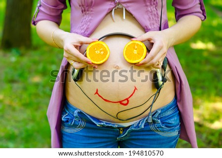 On the belly of a pregnant woman smiley face baby and headphones. The child listens to the music in the womb