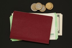 on the black surface is a bundle of bills, dollars and euros, on top is a red passport. there are several euro coins of different denominations nearby