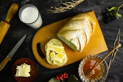On the black table is a Board with a cut loaf and a sandwich made of butter and honey. Next to it is a glass of milk, a rolling pin and a knife. At the bottom is a plate with butter and honey.
