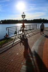 On the boardwalk, lit by a bright sunset, oncoming light, there are a bicycle rider, women and fishermen. The sidewalk is lined with beautiful red tiles.