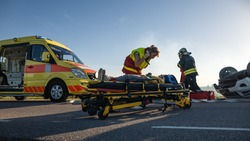 On the Car Crash Traffic Accident: Paramedics and Firefighters Rescue Injured Victims. Medics Give First Aid to a Little Girl on Stretchers.
