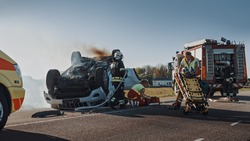 On the Car Crash Traffic Accident Scene: Team of Firefighters Rescue Injured People Trapped in Rollover Vehicle. Professionals Extricate Victims, give First Aid, Extinguish Fire