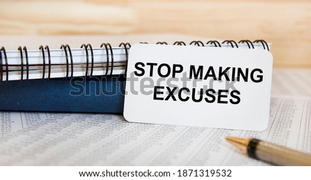 On the card text STOP MAKING EXCUSES, near diaries, reports and pen. Stock photo ©
