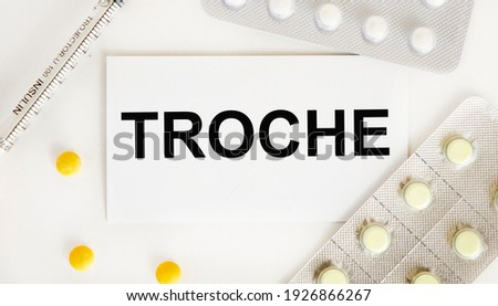 On the card text TROCHE, next to blisters with tablets and a syringe. Zdjęcia stock ©