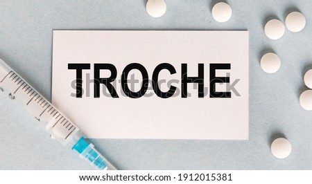 On the card text TROCHE, next to white tablets and a syringe. Zdjęcia stock ©