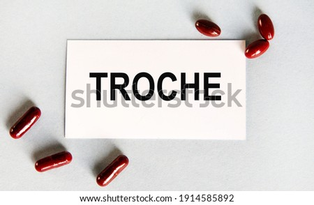 On the card the text of TROCHE, next to the sculpted red capsules. Zdjęcia stock ©