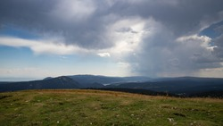 On the crest of the Jura mountains, between France and Switzerland, between earth and sky. Sky with dark clouds. Summer thunderstorm and backlight. Alpine lawn and rounded hills with a lake below
