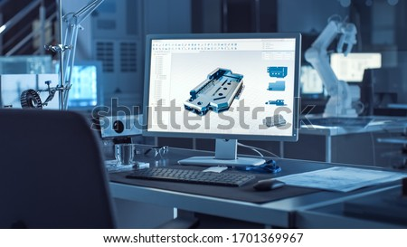 On the Desk Computer With CAD Software and Design of 3D Industrial Machinery Component. In the Background Robot Arm Concept Standing in Heavy the Dark.Industry Engineering Facility.