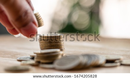 On the desk have coin pile and holding put down coin  on it. Concept Planning for spending and accumulating money Including paying taxes.  stock photo