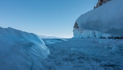On the frozen lake there are blue shiny ice hummocks. Icicles on a frozen rock base. Clear sky. Winter day. Baikal